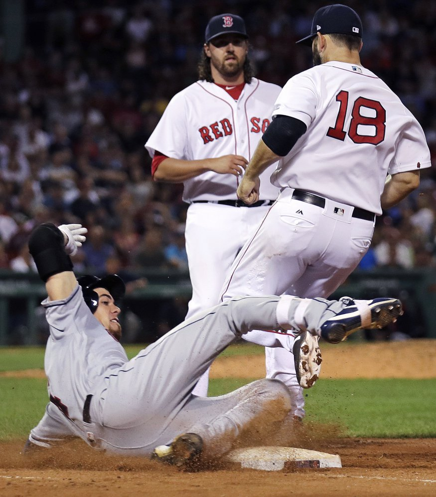 Cleveland Indians' Bradley Zimmer,  left, slides as he is forced out by Red Sox first baseman Mitch Moreland (18) on a ground-out during the seventh inning. Boston relief pitcher Heath Hembree, center, looks on.