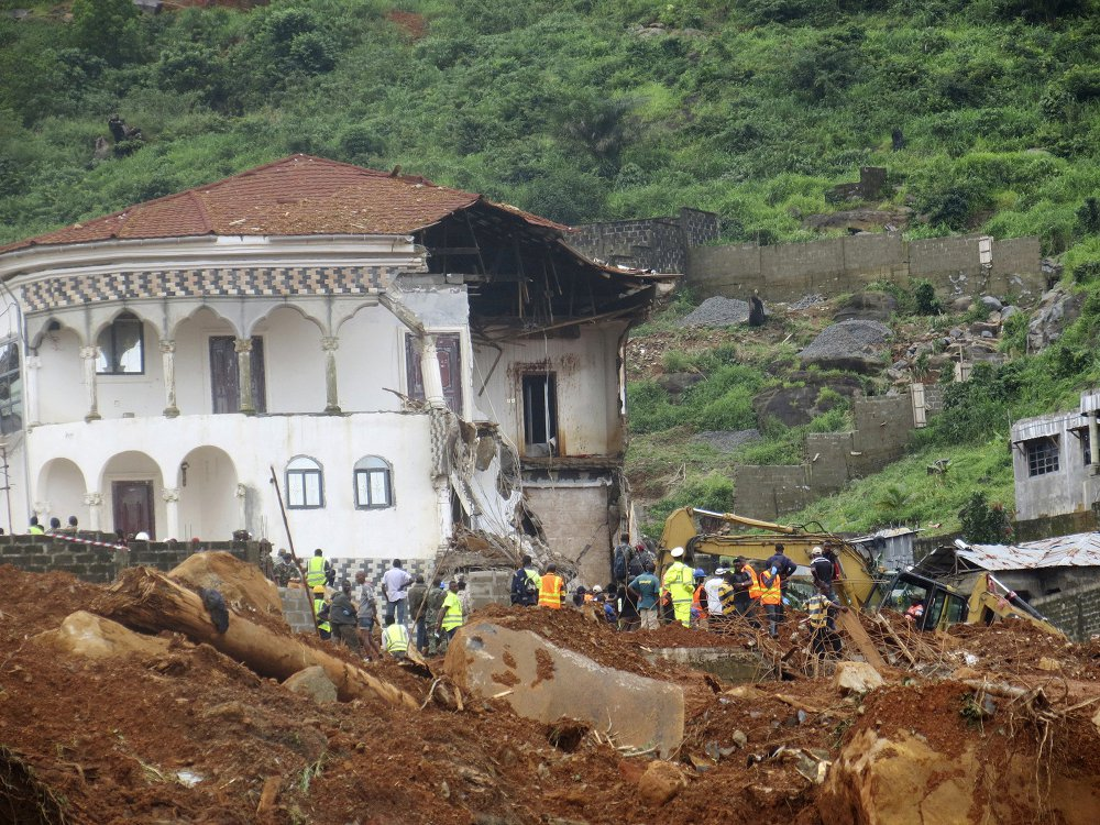 "Volunteers search for bodies at the scene of heavy flooding and mudslides in Regent, just outside of Sierra Leone's capital of Freetown. Survivors of deadly mudslides in Sierra Leone's capital are vividly describing the disaster as President Ernest Bai Koroma says the nation is in a ""state of grief."""