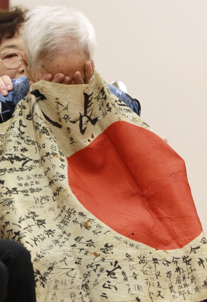 Sayoko Furuta, 93, reacts as she is covered with the Japanese flag that her brother brought to battle in the South Pacific.