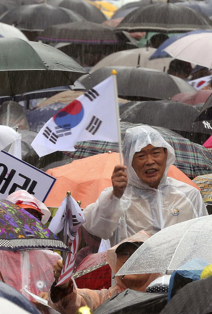 A South Korean waves a national flag during a Tuesday rally against North Korea's missile launches.