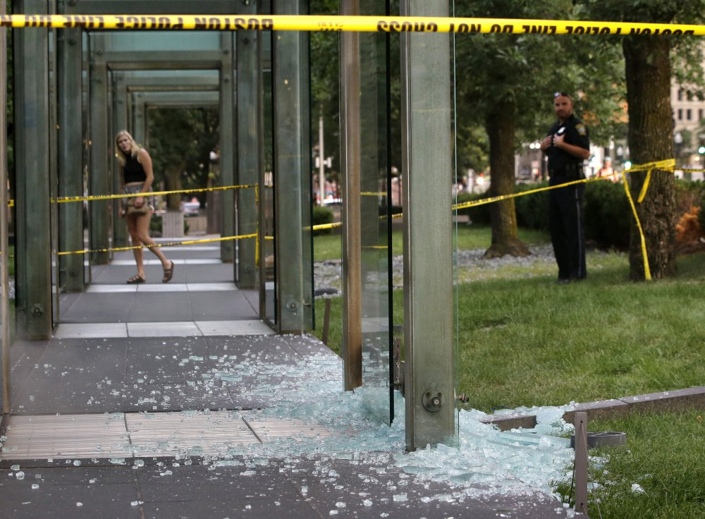 A passerby and a Boston police officer stand Monday near broken glass at the New England Holocaust Memorial. It was the second time the memorial has been damaged this summer.