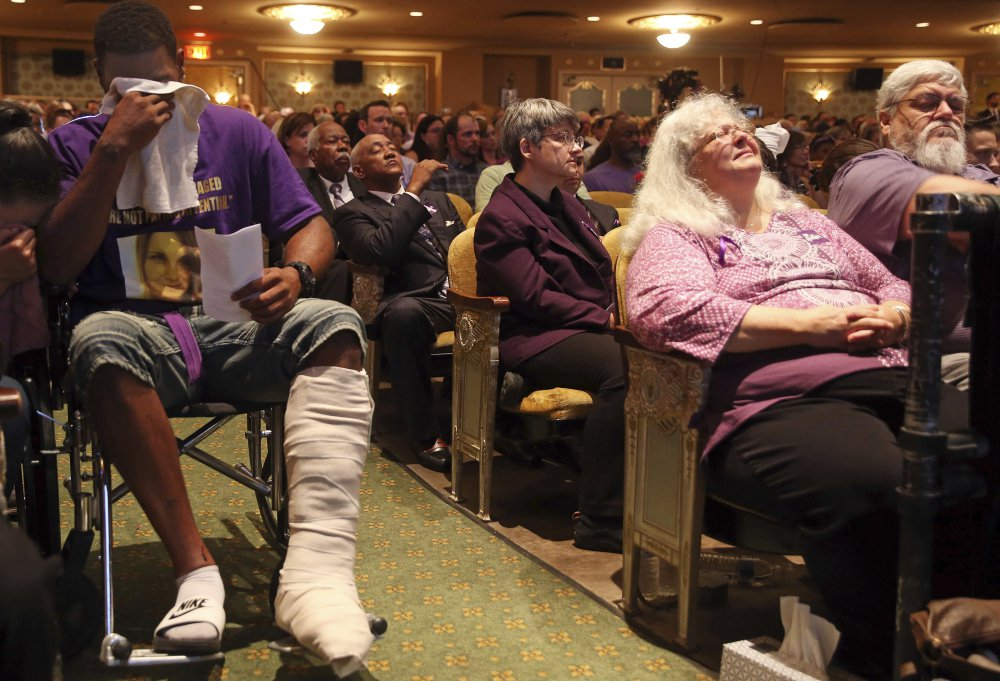 From left, Marcus Martin and Susan Bro, Heather Heyer's mother, listen during a memorial for Heyer on Wednesday at the Paramount Theater in Charlottesville, Va. Heyer was killed Saturday, when a car rammed into a crowd of people protesting a white nationalist rally. Martin pushed his fiancee out of the way of the vehicle that killed Heyer.