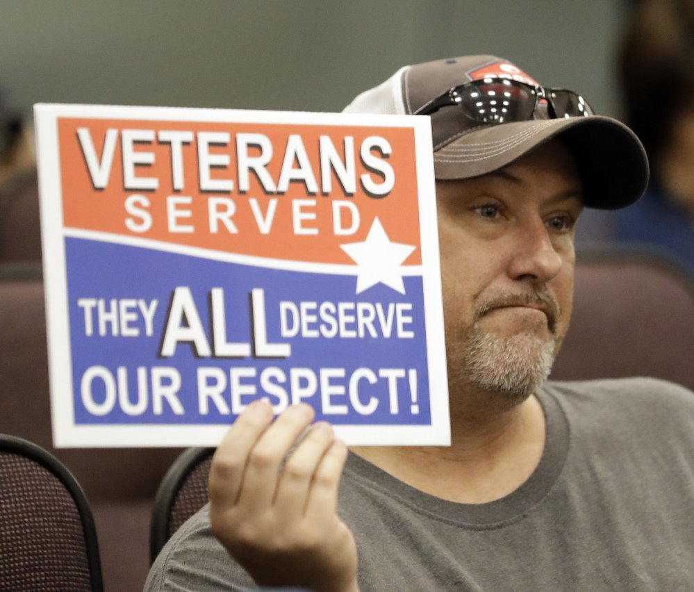 Steve Damron, 50, of Spring Hill, Fla., holds up a sign during a Hillsborough County Commission meeting about possibly moving a Confederate statue.