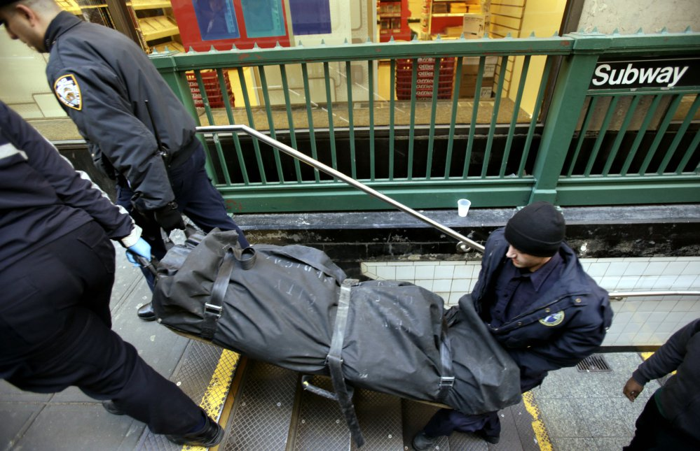 A police officer and medical examiner carry a body out of the Times Square subway station in New York after the man who died jumped into the path of an oncoming train.