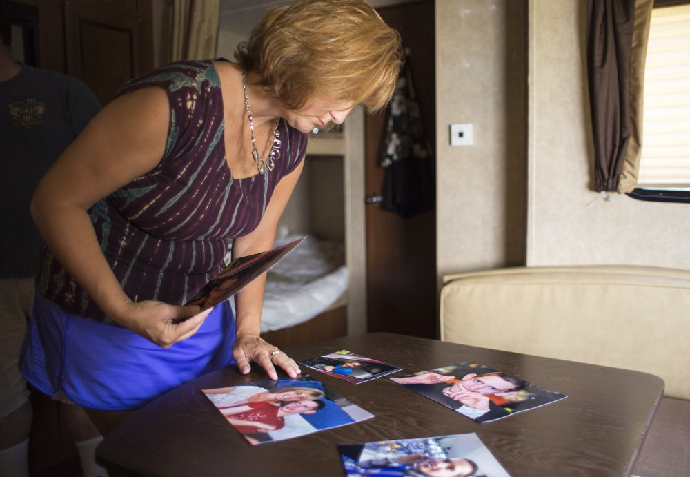ARUNDEL, ME - AUGUST 19: Terri Earley of Topsham looks through photos of her late son while vacationing in her camper in Arundel. Bradley LaPointe, who was diagnosed with autism spectrum disorder, was 22 when he died in a group home.