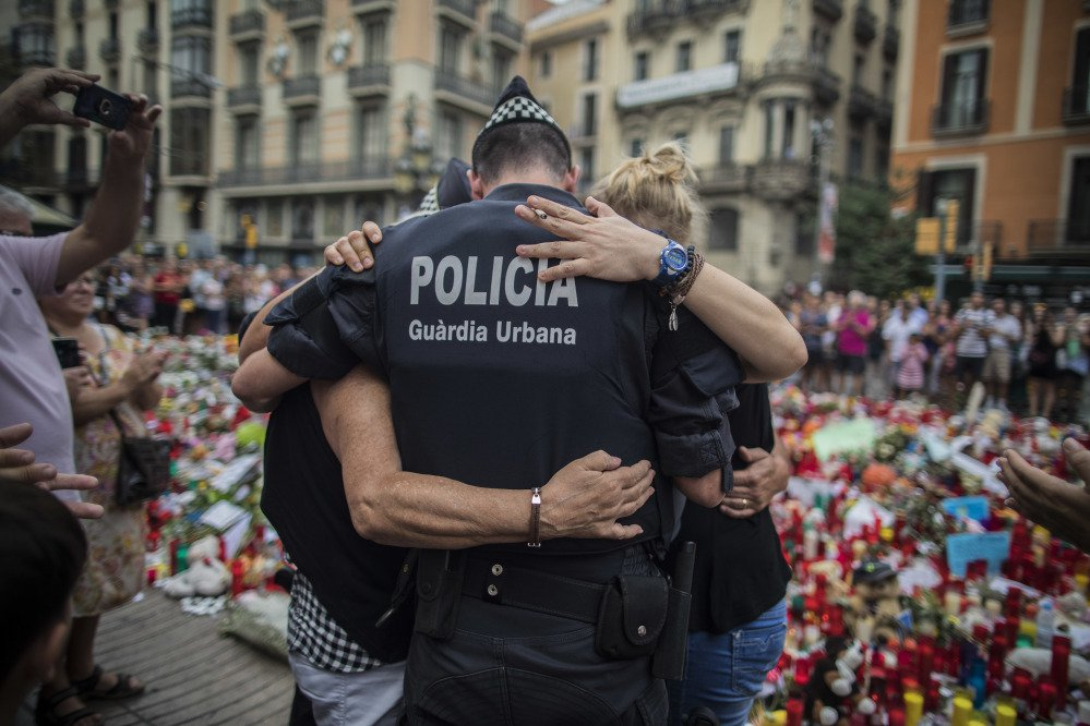 A policeman hugs a boy and his family, who he had helped during the terrorist attack, at a memorial to the victims on Las Ramblas, Barcelona, Spain, on Monday.