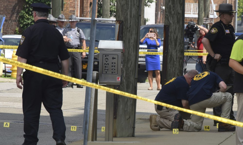 Evidence markers are placed on North Court Street and the sidewalk next to the Jefferson County Courthouse in Steubenville, Ohio, on Monday Aug. 21, 2017, after Jefferson County Judge Joseph Bruzzese Jr. was ambushed and shot early Monday morning.