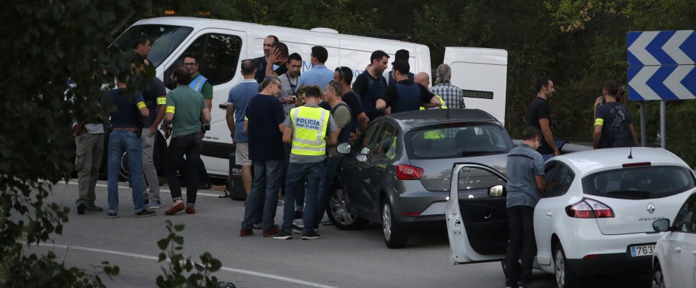 Spanish officials stand around a hearse Monday where police shot and killed Younes Abouyaaqoub, the last of the 12 suspects accounted for in Thursday's attacks in and around Barcelona that killed 15. Eight suspects are dead.