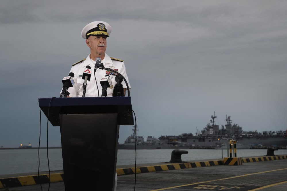 "Adm. Scott Swift, commander of the U.S. Pacific Fleet, answers questions at a press conference Tuesday with the USS John S. McCain and USS America docked in the background at Singapore's Changi naval base. Responding to Monday's fatal accident involving the McCain, he said, ""One tragedy like this is one too many."""