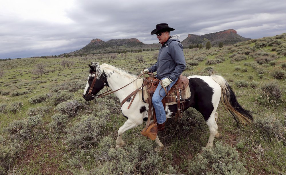 Interior Secretary Ryan Zinke rides a horse in the new Bears Ears National Monument near Blanding, Utah, in May. Zinke said Thursday that he won't seek to rescind any national monuments carved from wilderness and ocean by past presidents, but would press to change some boundaries and left open the possibility the Trump administration could allow new access to oil and gas drilling, logging and other industries.