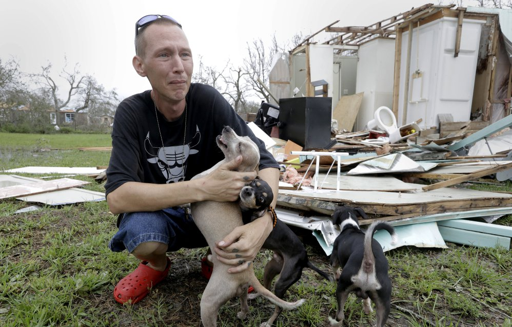Sam Speights tries to keep back tears while holding his dogs and surveying the damage to his home in the wake of Hurricane Harvey on Sunday in Rockport, Texas. President Trump was tweeting the unfolding events Sunday.