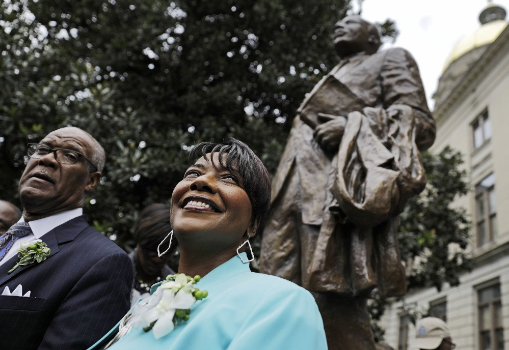 The Rev. Bernice King, daughter of the Rev. Martin Luther King Jr., stands under a statue paying tribute to her father after its unveiling on the Capitol grounds Monday in Atlanta.
