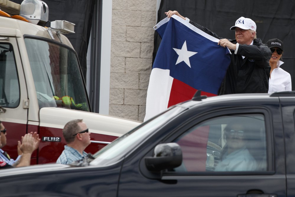 President Trump, accompanied by first lady Melania Trump, holds up a Texas flag after speaking with supporters outside Firehouse 5 in Corpus Christi, Texas, on Tuesday following a briefing on Harvey relief efforts.