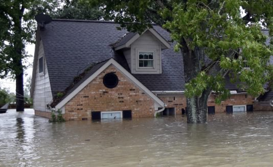 A home sits surrounded by floodwaters following heavy rains from Tropical Storm Harvey in Spring, Texas. Just 17 percent of homeowners in the counties suffering from Harvey flood damage have flood insurance, according to analysis of FEMA data.