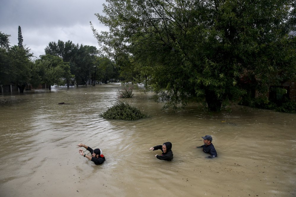 People wade through chest-deep water down Pine Cliff Drive in Houston on Tuesday as the Addicks Reservoir nears capacity because of record rains from Tropical Storm Harvey.
