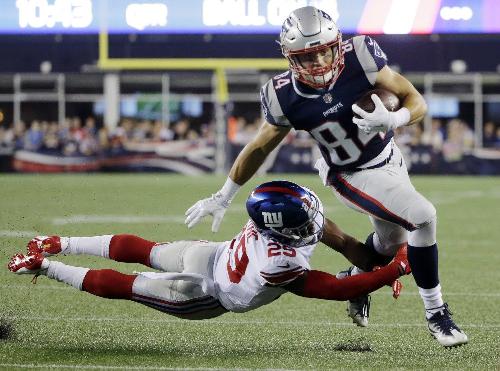 Patriots wide receiver Austin Carr slips an attempted tackle by Giants safety Nat Berhe on his way to a first-half touchdown Thursday night in Foxborough, Mass.