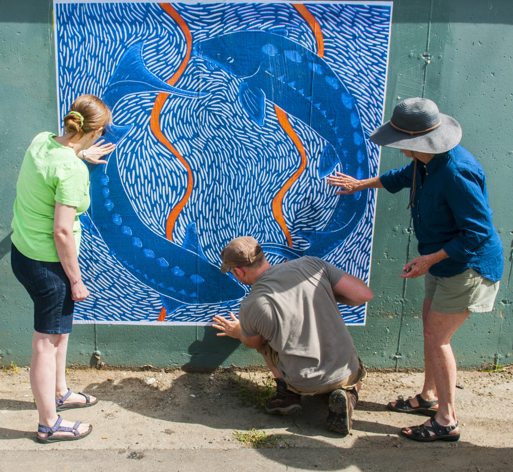 "From left, Barbara Whitten, Kerstin Gilg and Christine Olsen smooth out air bubbles after hanging a large-scale print Saturday on the bottom of Dennis' Pizza in the Arcade parking lot in Gardiner. The 6-by-6 foot print is of a 12-by-12-inch reduction linocut titled ""Endangered Shortnose Sturgeon,"" done by Olsen. It was the first of several new large-scale paper prints to be attached to several walls with wheat paste that day. The event was a preview of the next Artwalk Gardiner, which is scheduled for 5:30 to 8 p.m. Friday in downtown Gardiner."