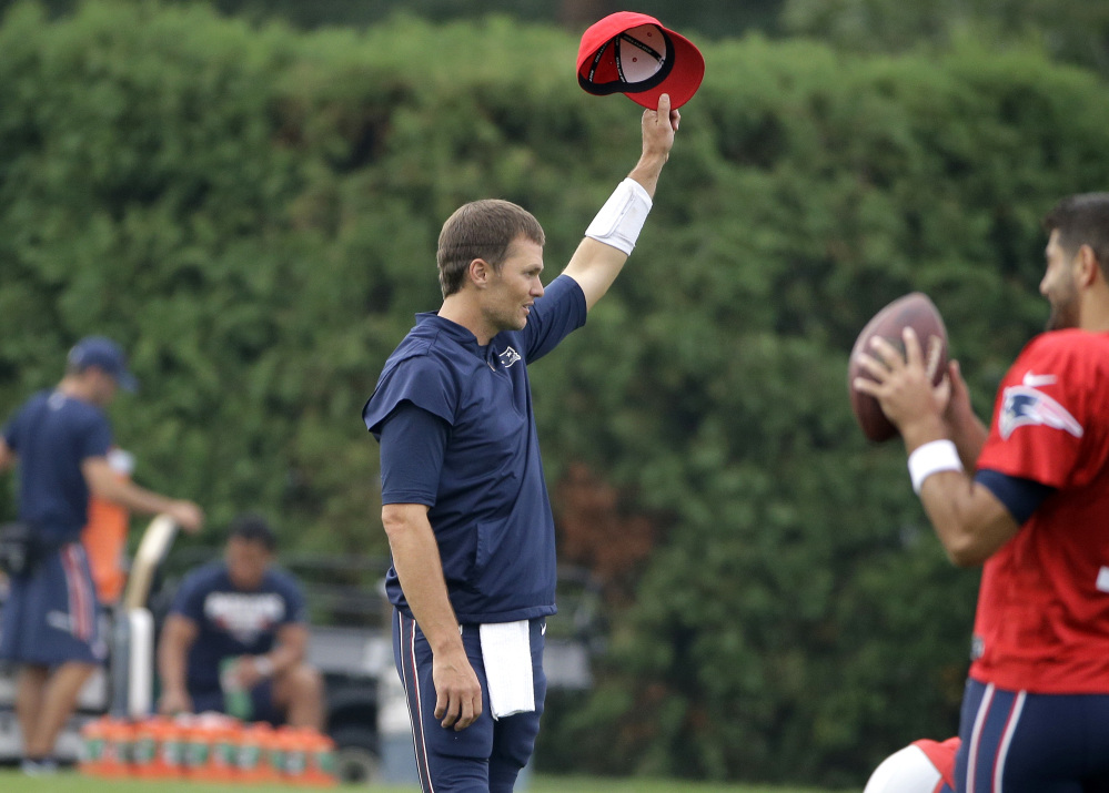 "New England Patriots quarterback Tom Brady removes his hat as a crowd of spectators sings ""Happy Birthday"" to him at training camp Thursday in Foxborough, Massachusetts."