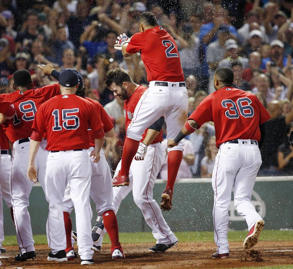 Boston Red Sox shortstop Xander Bogaerts (2) jumps as Mitch Moreland, center behind, crosses home plate on his walkoff home run during the 11th inning Friday against the Chicago White Sox in Boston.