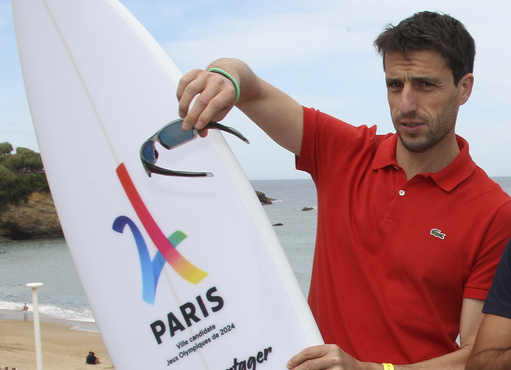 "Tony Estanguet, French canoe champion and co-president of the Paris candidacy for the 2024 Olympics and Paralympic Games, poses with a surfboard reading ""Paris candidate city Olympic Game 2024"" during World Surfing Games in Biarritz, southwestern France last month."