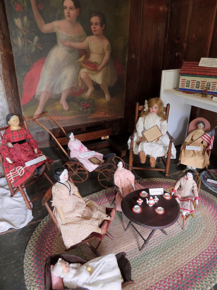 A selection of dolls arranged before a painting of children who lived at the Pownalborough Court House in the mid 1800s were common over the course of nearly 100 years. The dolls and other toys will be on exhibit until Columbus Day.