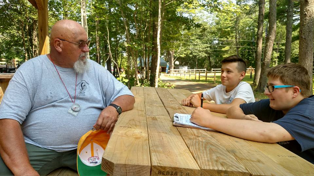 Ken Flagg, of Strong, left, being interviewed by Boy Scout Reporters Braden Mayo, center, and Ben Lamontagne, right, both of Oakland, at Camp Bomazeen in Belgrade.