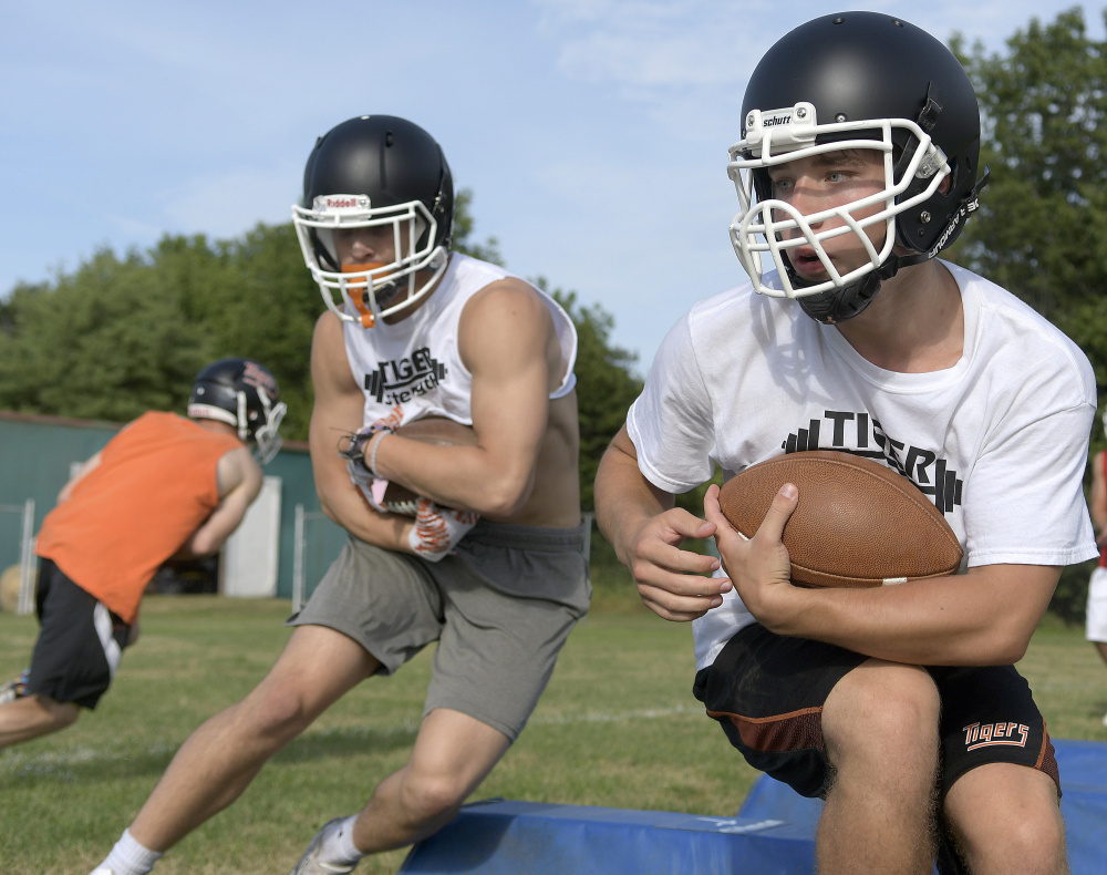 Members of the Gardiner football team run through a drill during training camp last month.