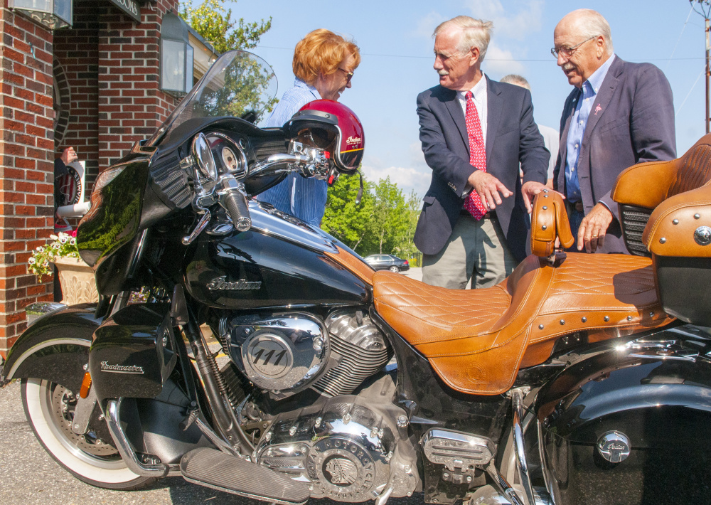 Ellen Crocker, left, Sen. Angus King, independent of Maine, and Gary Crocker talk about the Crockers' Indian motorcycle after King's speech on Wednesday at the Senator Inn and Spa in Augusta. Crocker said that the two men and some other friends are planning a motorcycle trip around Maine this weekend like they used to do when King was the governor.