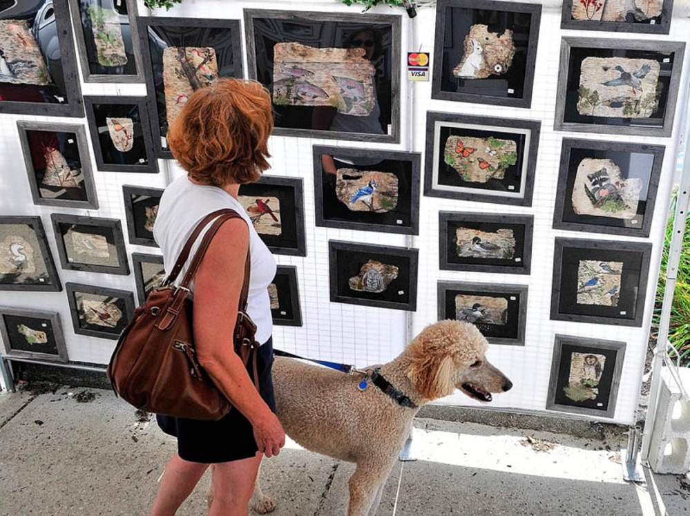 Debbie Farrell and her poodle Rigby look at Sharon Boody-Dean's paintings on birch bark during the 26th annual Winthrop Sidewalk Art Show on August 17, 2013, in downtown Winthrop.
