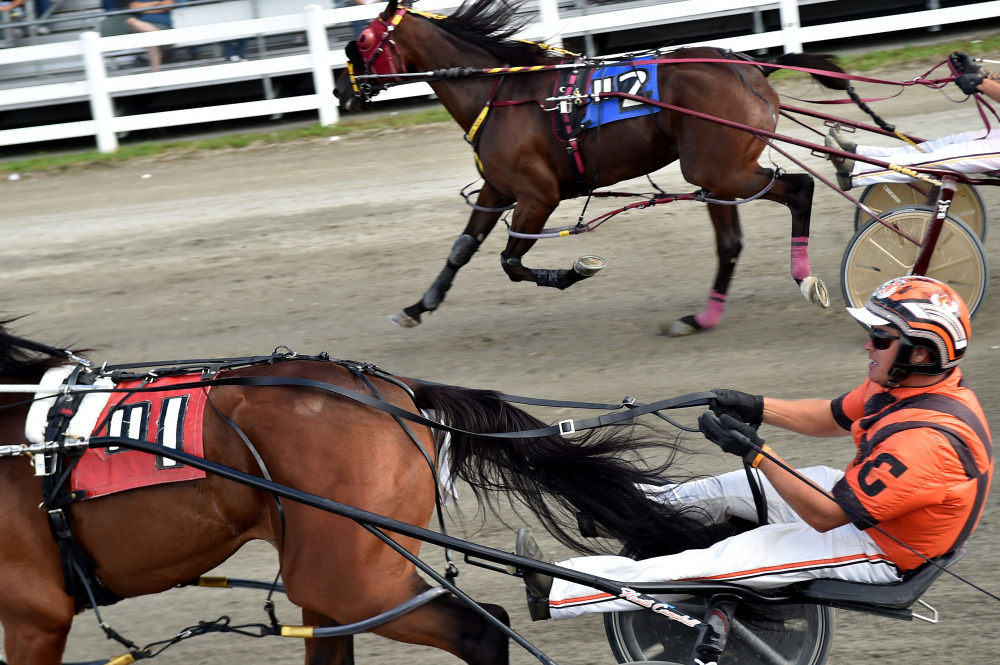 Heath Campbell, bottom, drives Bet You past beat Ron Cushing to win the Walter Hight Invitational at the Skowhegan Fairgrounds last year.