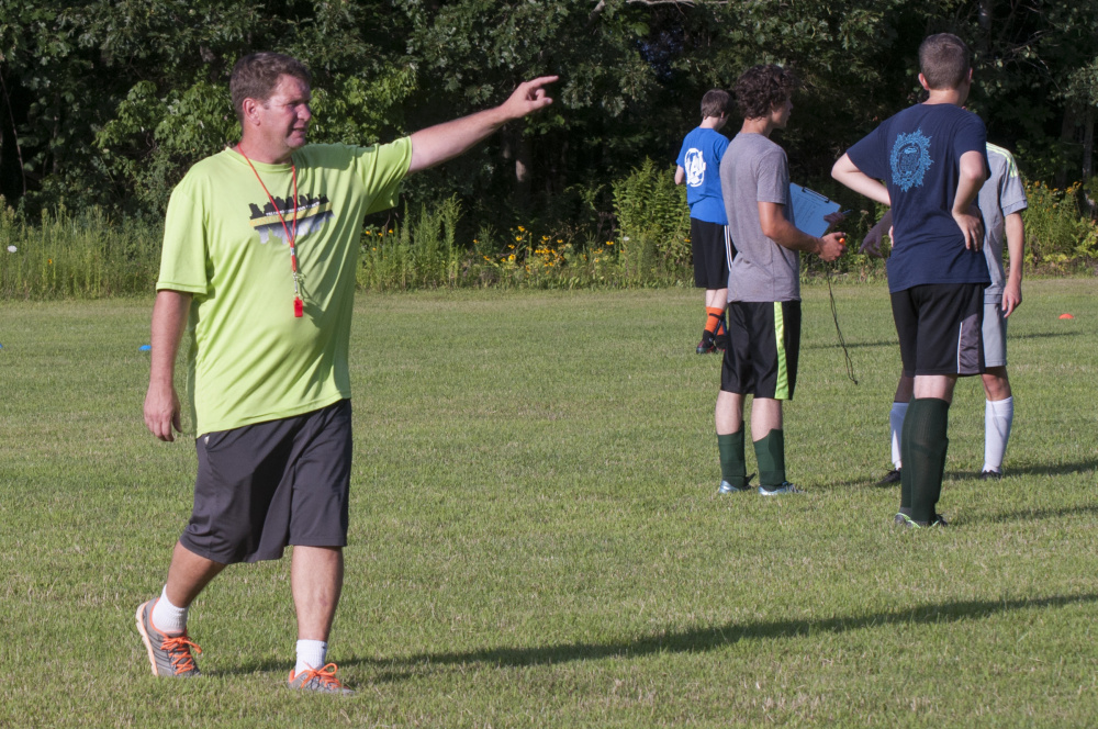Phil Hubbard gives instructions to the Temple Academy boys soccer team during practice on Monday at Thomas College in Waterville.