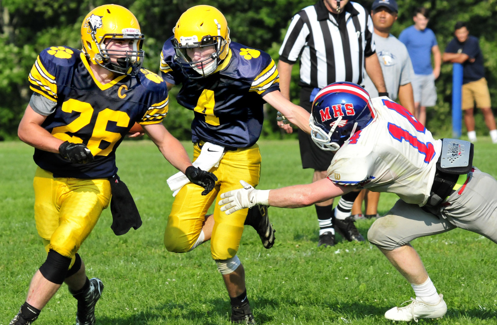 Mt. Blue's Noah Bell, center, evades a Messalonskee player during a scrimmage Monday in Oakland.
