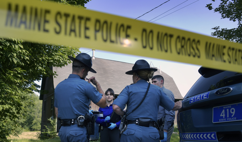 State troopers and detectives confer Monday outside a residence in Litchfield where a man was reportedly shot.