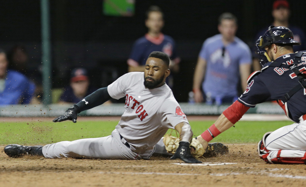 Boston Red Sox outfielder Jackie Bradley Jr. slides safely into home plate as Cleveland catcher Yan Gomes is late on the tag in the seventh inning Tuesday in Cleveland. Bradley Jr. scored on a two-run double hit by Eduardo Nunez.