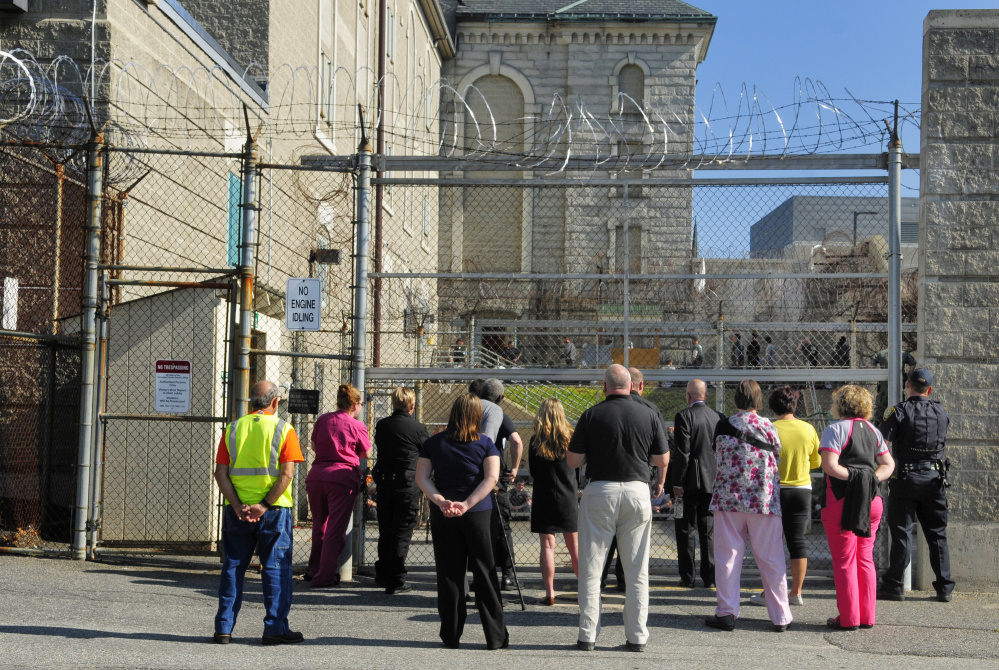 People watch from the parking lot as inmates are counted in the fenced in recreation yard during a drill Thursday at the Kennebec County jail in Augusta.