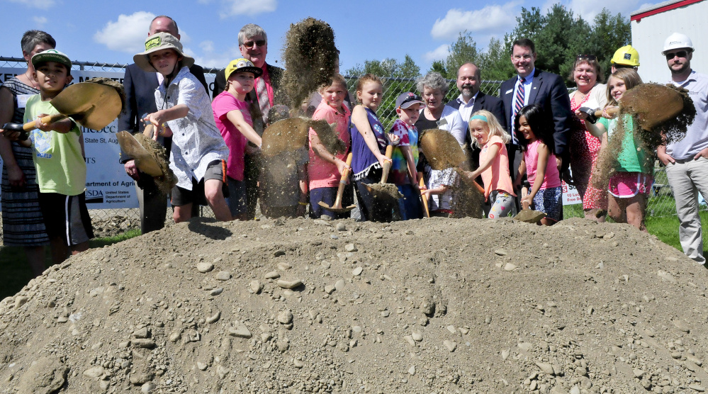Students who attend Kennebec Montessori School joined school, local and federal officials in pitching in some dirt during a groundbreaking ceremony for the USDA financed expansion project at the Fairfield school Thursday.