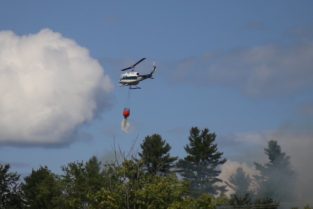 A Maine Forest Service helicopter drops water on a fire off Overlook Drive in Hallowell Friday. The helicopter first pulled water from the Kennebec River and then dropped it on the fire.