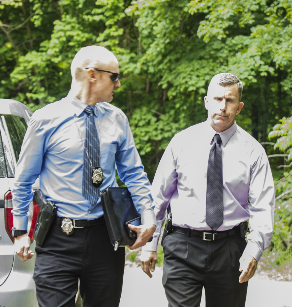 Detective Benjamin Sweeney, left, and Sgt. Christopher Tremblay, both of the Maine State Police, confer in June at the scene of a fatal shooting off Yeaton Drive in West Gardiner. Police said the victim, James Haskell, 41, was a visitor at the property.
