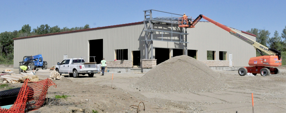 Workers build the new Maurice's & Son auto shop on College Avenue in Waterville on Monday.