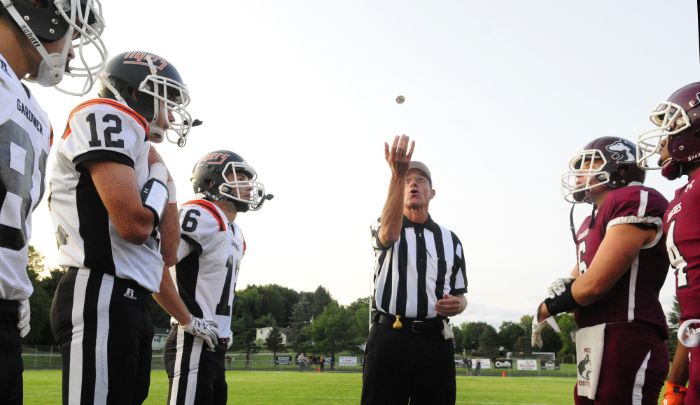 Referee Ed Bear tosses a coin at Hoch Field in Gardiner prior to the start of a Gardiner-Maine Central Institute preseason game last Friday.