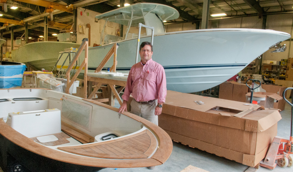 Southport Boats Vice President and General Manager George Menezes stands between a 16-foot Carbon Craft yacht tender, front, and 33-foot Southport center console boat Tuesday at Southport in Augusta, the day an expansion and sale was announced.
