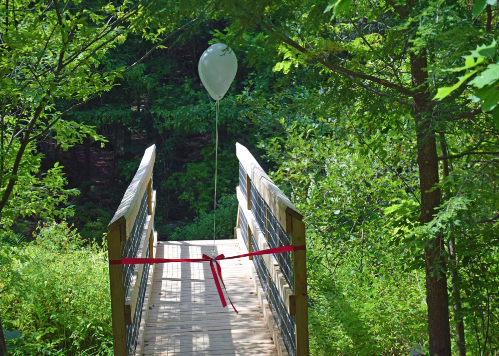 The bridge is located in the Augusta Nature Education Center at the South Belfast Avenue visitor entrance near Whitney Brook.