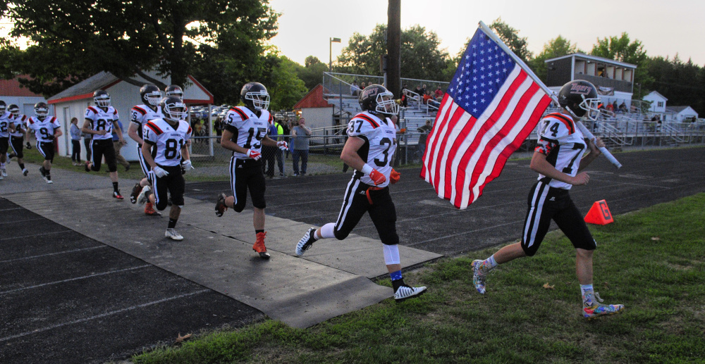 Isaac Dearborn, far right, leads the Gardiner football team onto Hoch Field prior to an Aug. 25 exhibition game against Maine Central Institute.