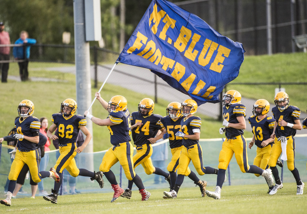 Members of the Mt. Blue High football team run onto Caldwell Field in Farmington prior to an Aug. 25 exhibition game against Nokomis.
