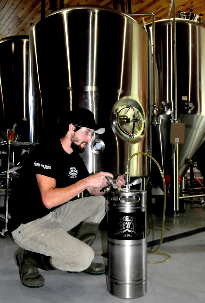 Bigelow Brewing Co. assistant brewer Colin Hoffman transfers on Thursday the company's La Saison du Labrador beer, specially brewed for the Skowhegan Craft Brew Festival, from a brite tank to a small keg for the festival this Saturday.