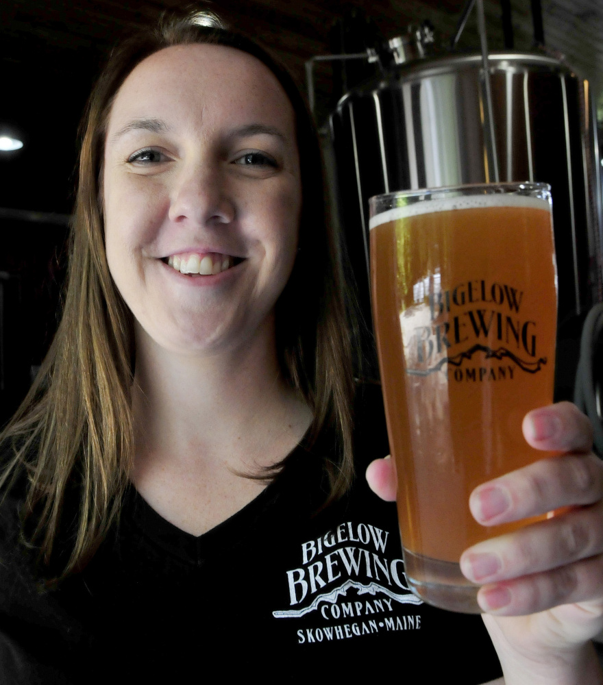 Bigelow Brewing Co. employee Jordan Powers shows off the color of La Saison du Labrador beer on Thursday. A collaboration of Bigelow and a Quebec brewery, La Saison was brewed especially for the Skowhegan Craft Brew Festival this Saturday.