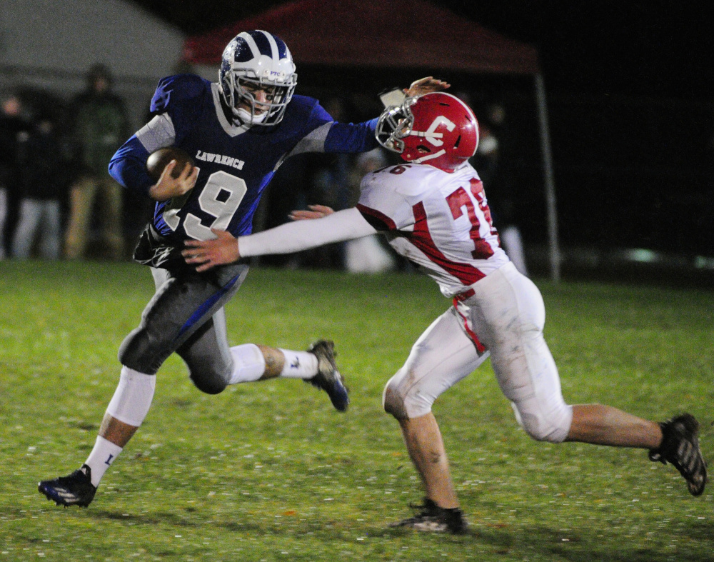 Lawrence running back Braden Ballard, left, stiff arms Cony defender Nic Mills during a Pine Tree Conference B quarterfinal game last season in Fairfield.