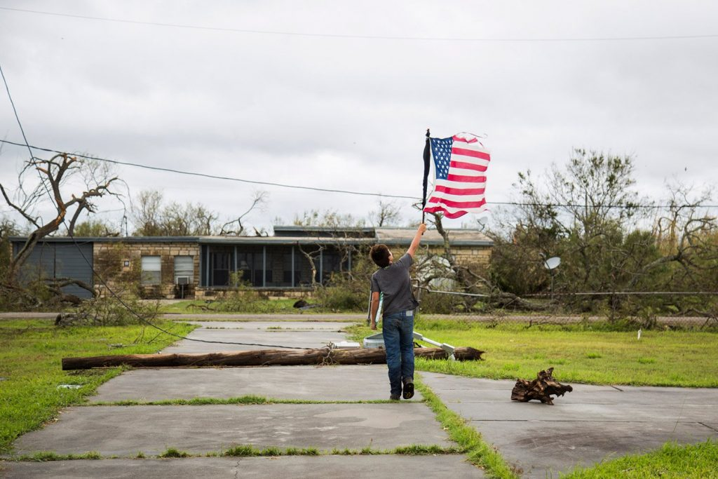 Layton Carpenter walks down a debris-littered driveway in Bayside, Texas, on Sunday holding a broken American flag that he found in the water after Hurricane Harvey hit.