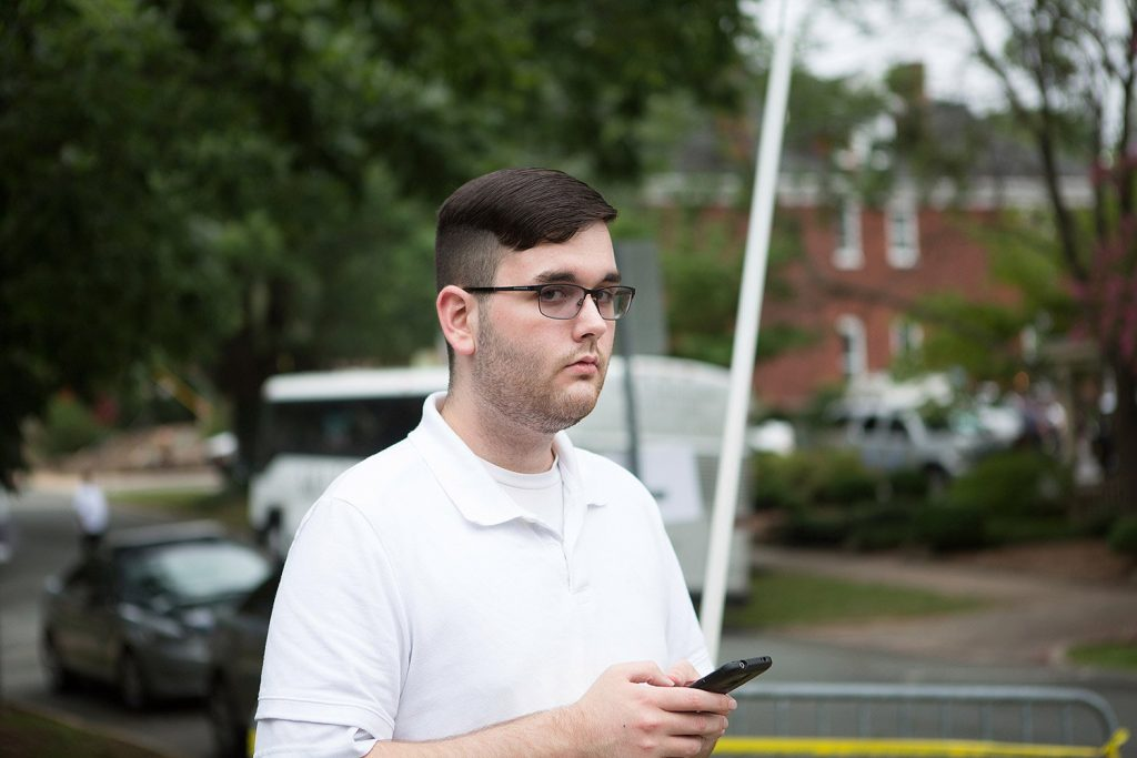 James Alex Fields Jr. stands on the sidewalk looking at the procession of clergy as they gathered at McGaffey park prior to a rally in Charlottesville, Virginia, on Aug. 12. Fields is accused of ramming his car into a crowd of counter-protesters, killing 32-year-old Heather Heyer and injuring over a dozen others.