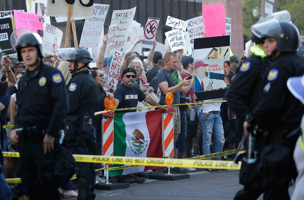 People protest outside the Phoenix Convention Center during his rally Tuesday night.